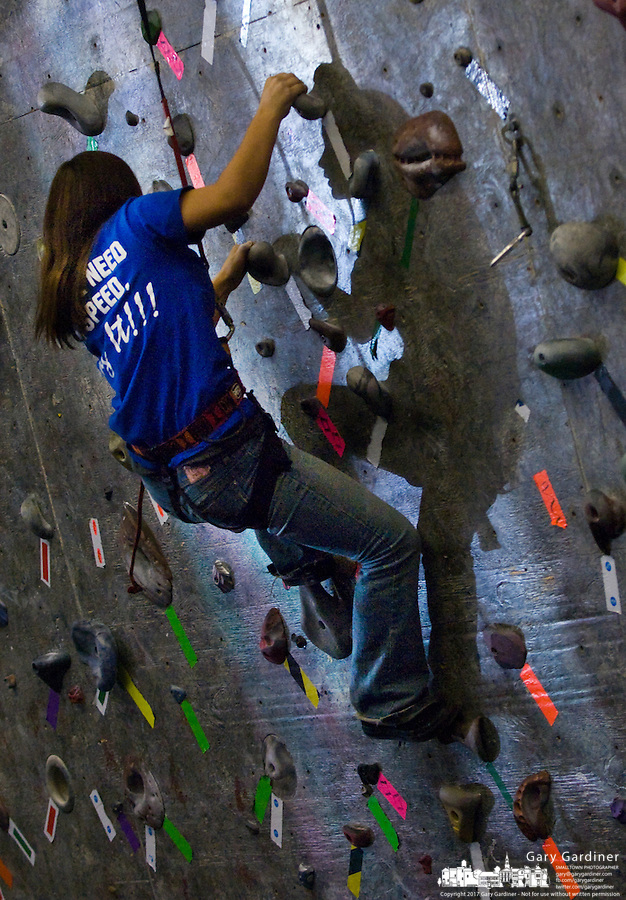 A young girl moves up an indoor climbing wall.