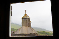 Old window with ripples showing age framing chapel at Fort Ross State historic Park. California