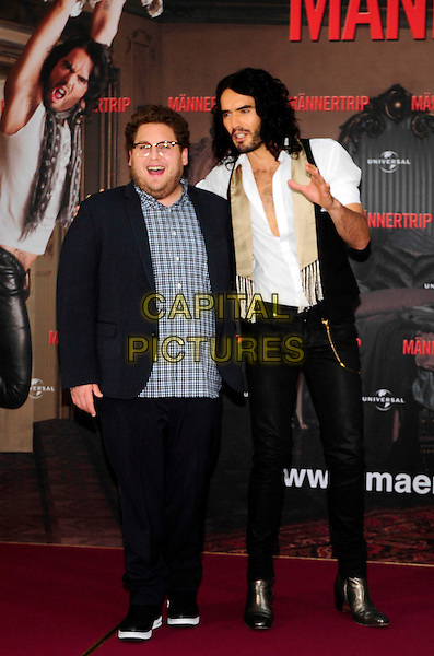 "JONAH HILL & RUSSEL BRAND.Photocall for ""Get Him To The Greek"", Hotel Adlon, Berlin, Germany..June 25th, 2010.full length black trousers jeans denim blue check shirt gold boots shoes white shirt beige scarf tights beard facial hair glasses arm over shoulder unbuttoned hand mouth open.CAP/PPG/NK.©Norbert Kesten/People Picture/Capital Pictures"