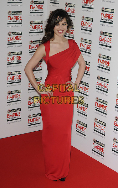 Berenice Marlohe.The Jameson Empire Film Awards 2012, Grosvenor House Hotel, Park Lane, London, England..March 25th, 2012.full length red dress off sleeve shoulder hands on hips.CAP/CAN.©Can Nguyen/Capital Pictures.