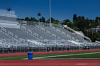 A young woman runner, training for a marathon, runs alone on a high school track, passing the empty stadium stands while working on her speed.