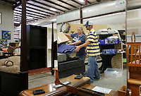 NWA Democrat-Gazette/DAVID GOTTSCHALK  Lucie Dalton (left), warehouse assistant, and Tyler Sibert, a volunteer, are reflected in a mirror as they arrange bedding in the display area of the Habitat for Humanity ReStore of Washington County in Fayetteville Monday, August 3, 2015. The store is open Monday - Saturday 9:00 a.m. to 5:30 p.m., and features new and used furnishings and commercial and home building materials.