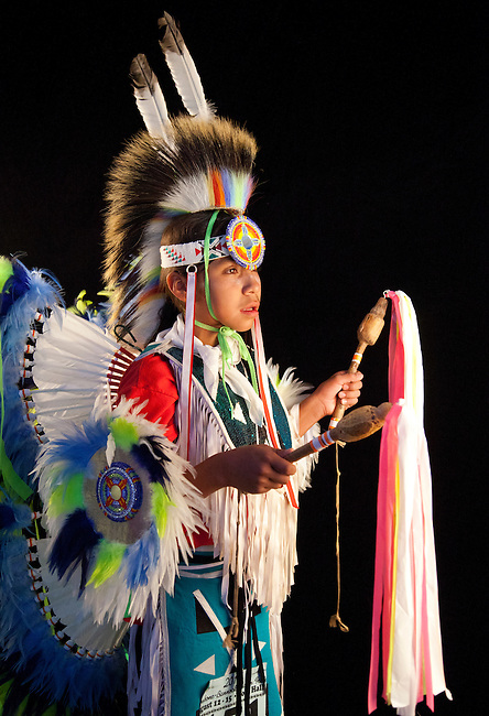 Fancy bustle dancer Pacer Allan Tobey (Assiniboine/Sioux) dressed in pow wow regalia of colorful feathered bustles, apron and roach headdress holds two dance sticks with streamers.