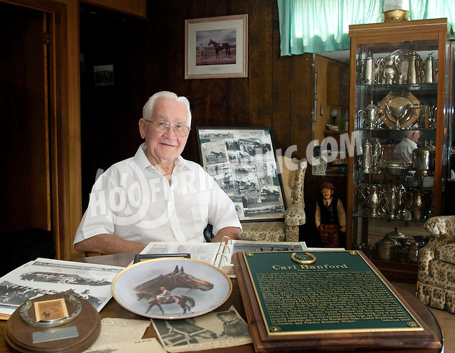 Hall of Fame trainer Carl Hanford at his home with some of his awards