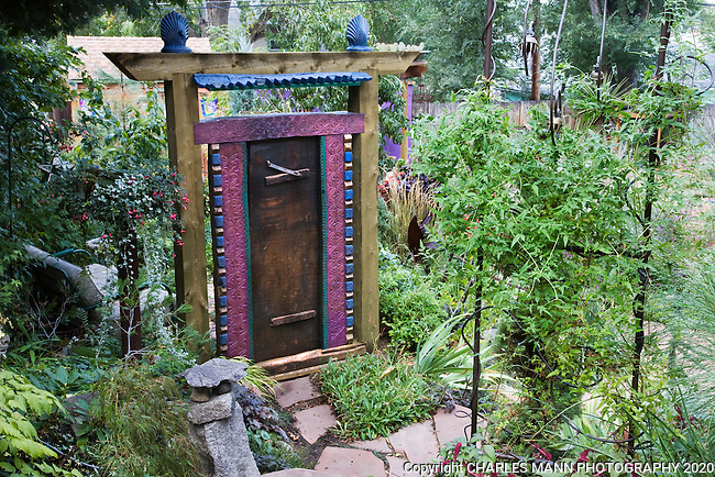 In hisDenver garden, Dan Johnson used a freestanding wooden door and frame to crate a sense of mystery and drama while dividing the backyard garden from the side yard which approaches it.