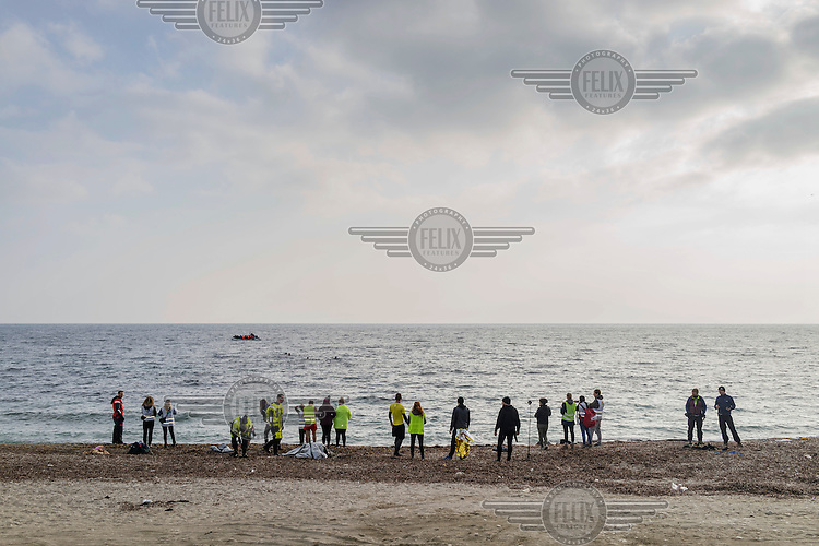 Members of the media, NGOs, Greek recyclers, Spanish lifeguards and staff from the UNHCR wait for a boat carrying refugees to arrive on the beach.