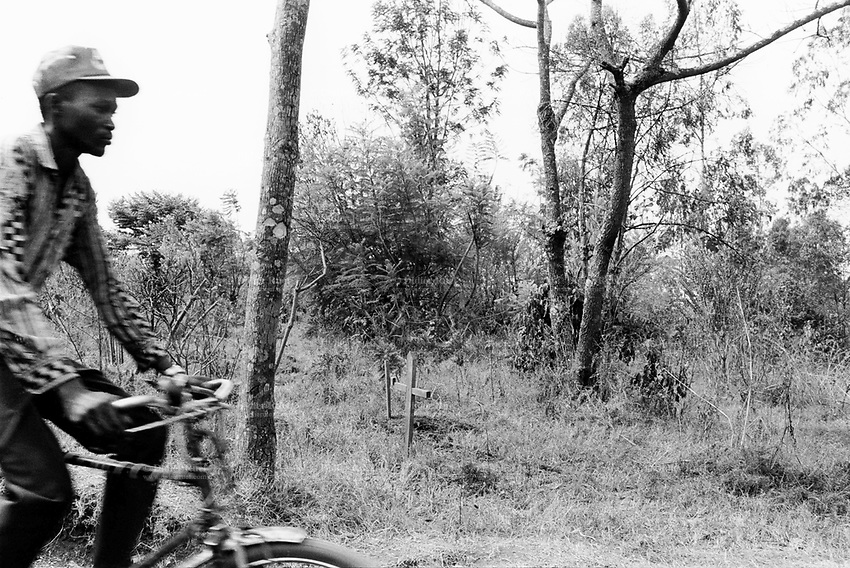 Burundi. Karuzi Province. Buhiga. Man on bicycle passes by a graveyard where are buried victims from the 1993 genocide in which thousands of Hutus were killed by Tutsis.  © 2000 Didier Ruef