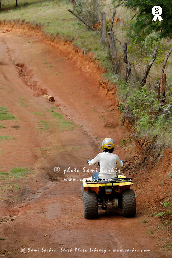 Mature woman riding quadbike on dirt road, rear view (Licence this image exclusively with Getty: http://www.gettyimages.com/detail/200503586-001 )