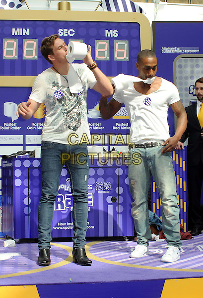 LEE RYAN & SIMON WEBBE of BLUE .Blue at the Cadburys Spots and Stripes Toilet Roll Challenge at Westfield Shopping Centre, London, England, UK,16th April 2011..full length sitting white grey gray t-shirt jeans loo roll in mouth funny .CAP/WIZ.© Wizard/Capital Pictures.