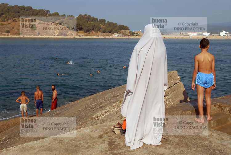 - bathing young people and veiled woman on waterfront of Tabarka town....- giovani bagnanti e donna velata sul lungomare della città di Tabarka