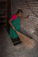 Bangladesh, Jhenaidah. Chaklapara sweeper colony. Alo is Dalit Hindu, or the untouchable caste working as sweeper. There are about 5.5 million Dalit across the country, they are most neglected caste in their society. Alo, works in government job as a sweeper for about 4-5000 TK a month, about US$50 a month. She gets up before dawn to sweep out the office buildings and shops in town Model released.