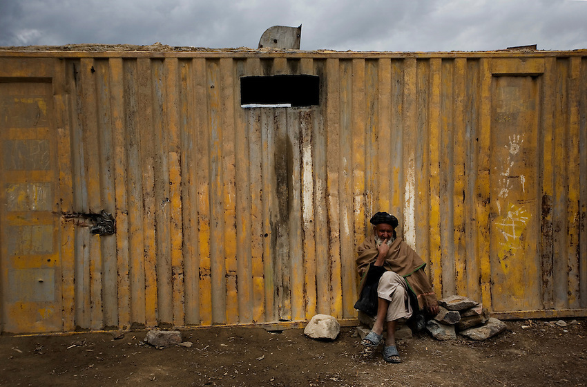 An Afghan man sits outside his shop in Charkh, Afghanistan, Sunday, May 3, 2009.