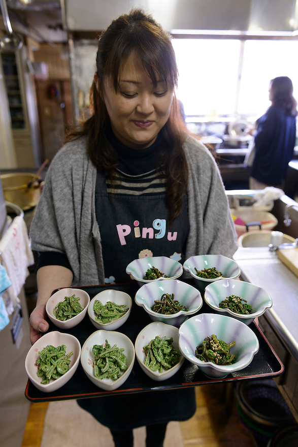 A member of staff at the Ashiya guesthouse holding a tray of cooked mountain vegetables. Tsuruoka, Yamagata Prefecture, Japan, April 9, 2016. The city of Tsuruoka in Yamagata Prefecture is famous for its sansai mountain vegetable cuisine. These foraged grasses, fungi and vegetables are also used by the mountain ascetics of the Shugendo religion.