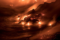 Glowing molten lava pours into the Pacific Ocean throughout the night, creating land, steam and sound, Hawai'i Volcanoes National Park, Puna district, Big Island of Hawai'i, September 2017.