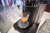 "A Nespresso brand single-shot coffee brewer pours an espresso at a promotional event in New York on Thursday, February 20, 2014. The single-cup machines use Nespresso ""capsules"" which contain a single serving of coffee. They are in direct competition with Green Mountain Roasters, using Keurig pods,  which controls a 90% share of the US market. (© Richard B. Levine)"
