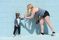 Tonia Hanson (right), owner of Tonia Hanson Photography in Fayetteville, gets a high five Thursday, May 21, 2020, from Charleston Smolinski, 3, while taking family photographs with Charleston's twin brother, Roman, and mother, Ally Smolinski of Rogers, in front of the Maude Wall at Maude Boutique in Fayetteville. The clothing store invites patrons to use their multicolored back wall for photographs. Visit nwaonline.com/200522Daily/ for today's photo gallery.<br /> (NWA Democrat-Gazette/Andy Shupe)
