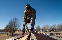 NWA Democrat-Gazette/CHARLIE KAIJO Luis Miguel of Springdale lays out metal roofing on Thursday, January 4, 2018 at Outside The Box NWA flea market in Rogers.<br />