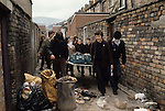 Ireland The Troubles. Belfast 1980s. Teenage Catholic youths collect material to make  petrol bomb. Milk bottles are filled with petrol and a bung of material is lit and the bomb then thrown at the British Army soldiers.