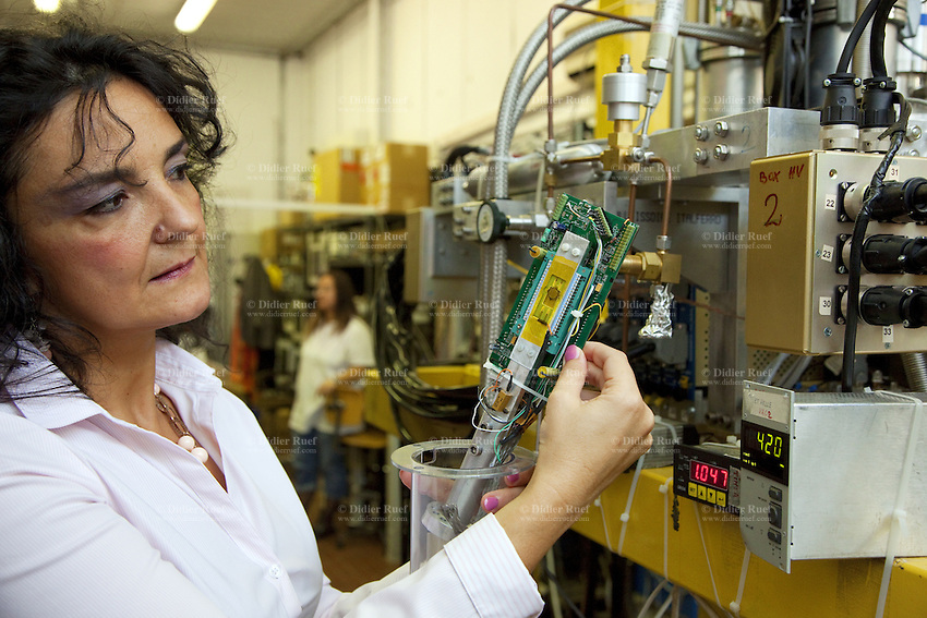 Italy. Lazio region. Frascati. Laboratori Nazionali di Frascati (LNF). Istituto Nazionale di Fisica Nucleare (INFN). Catalina Curceanu, a romanian citizen and nuclear physicist, is standing in the Siddharta laboratory. Siddharta means Silicon Drift Detector for kahonic atom research by timming application.  Siddharta is an experience measurement of exotic atoms ( Kaonic atoms). Catalina Curceanu holds in her hands a Silicon Drift Detector and Electronics. The INFN - the National Institute of Nuclear Physics - is an organization dedicated to the study of the fundamental constituents of matter, and conducts theoretical and experimental research in the fields of subnuclear, nuclear, and astroparticle physics. Fundamental research in these areas requires the use of cutting-edge technologies and instrumentation, which the INFN develops both in its own laboratories and in collaboration with the world of industry. Frascati is a town and comune in the province of Rome. It is located 20 kilometres south-east of Rome. Frascati is closely associated with science, being the location of several international scientific laboratories. Romanian immigration. 30.09.2011 © 2011 Didier Ruef