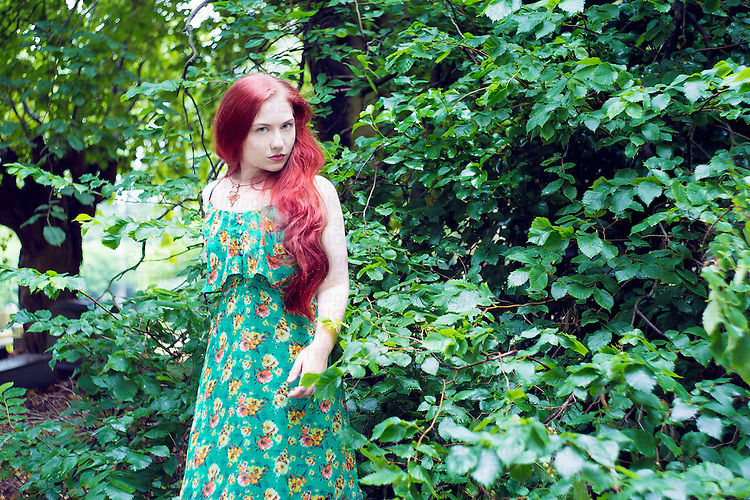 Female 20-25 years of age with long red hair wearing flowery summer dress and necklace standing looking at camera