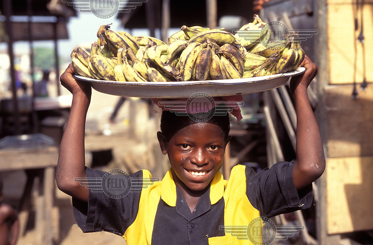 ©Giacomo Pirozzi/Panos Pictures..Nigeria. Boy selling bananas in the market in the slums.