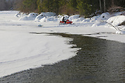 A snowmobile makes his way off Newfound Lake and into Wellington State Park during the winter months.. Located in Bristol, New Hampshire USA.