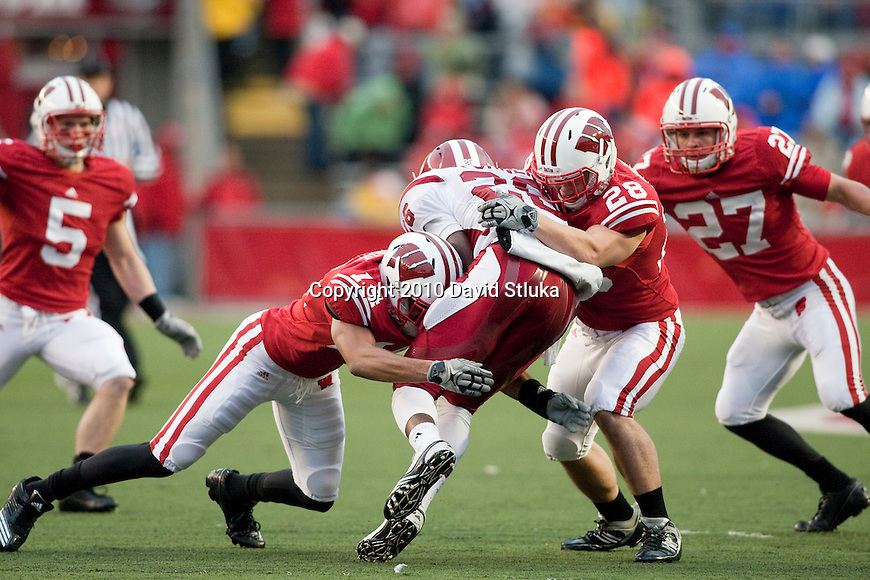 Wisconsin Badgers defensive back Marcus Cromartie (14) and linebacker Coddye Ring-Noonan (28) tackle running back Nick Turner (26) during an NCAA college football game on November 13, 2010 at Camp Randall Stadium in Madison, Wisconsin. The Badgers won 83-20. (Photo by David Stluka)