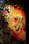 Bao-jhong Yi-min Temple, Kaohsiung -- Sunlit Chinese characters on a temple pillar.