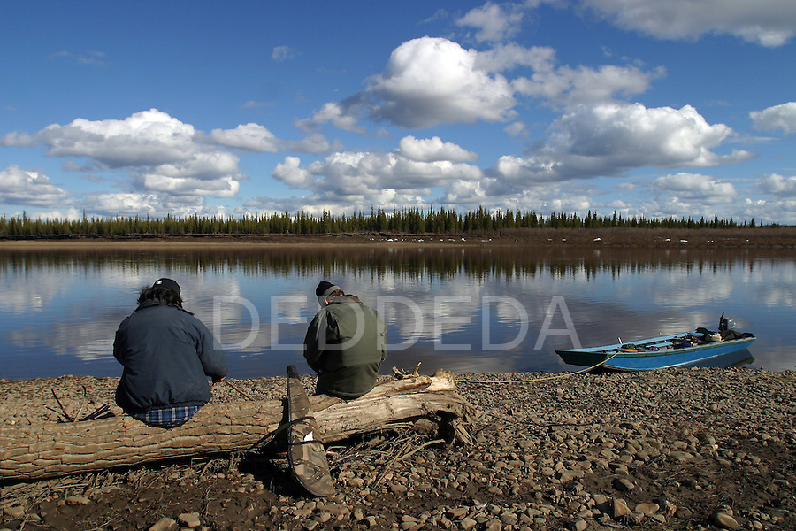 Vuntut Gwitchin First Nation member, Joel Peter, and journalist, Paul Salopek, sit along the riverbank of the Porcupine River near Old Crow, Yukon Territory, Canada, as they wait for caribou to cross.
