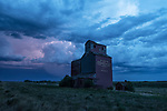 Abandoned grain elevator in rural Saskatchewan with a storm and lightning behind it creating a dramatic, awe inpsiring scene.