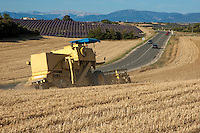 Combine harvester in a wheat field with rural landscape in background, Valensole, Provence, France.