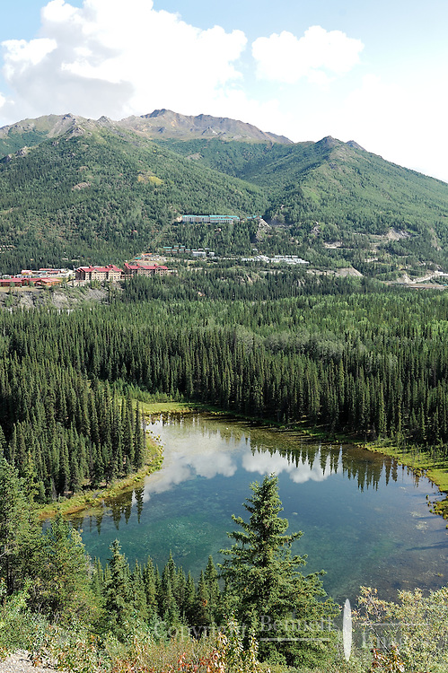 """Multiple hotels are clustered near the entrance to Denali National Park in an area Alaskans call """"Glitter Gulch."""" Horseshoe Lake is in the foreground. The Alaska Railroad's Denali Star train runs between Anchorage and Fairbanks, with Denali one of the stops along the way."""