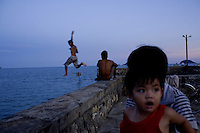 Children jump off of Pier 914 on Con Son Island, part of Con Dao Islands in Vietnam. The pier is named after the number of prisoners who were killed during the construction process. Photo taken Thursday, May 5, 2010...Kevin German / LUCEO For the New York Times