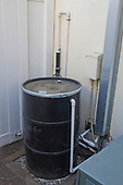 50 gallon rain barrel holding filtered water from rainwater harvesting system at Green home that is off the grid. Solar power and a rainwater harvesting system supply all the energy and water for this home in Los Angeles, California, USA