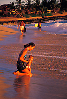 EDITORIAL ONLY. Mother and baby play by the ocean at sunset. Makaha, Oahu