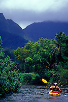 Woman paddling kayak on the Hanalei River with jungle and Mount Waialeale in background, Kauai, Hawaii