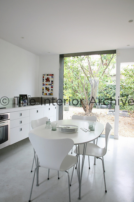 This all white kitchen opens onto a garden of cherry trees and has work surfaces in brushed stainless steel and a table and chairs by Arne Jacobsen for Fritz Hansen