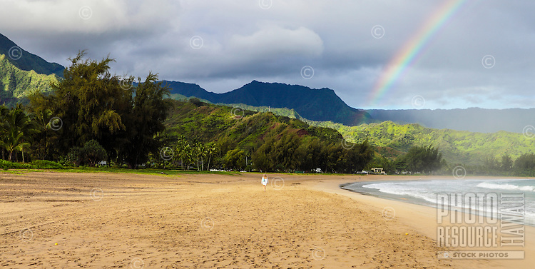 A woman enjoys the morning with a rainbow at Hanalei Beach and Hanalei Bay, Kaua'i.