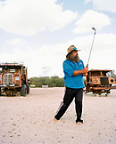 AUSTRALIA, Mungerannie, the outback, mature man standing with golf club in hand, two junk trucks in background