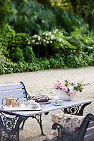 Afternoon tea is served al fresco on a outdoor table adorned with freshly cut roses