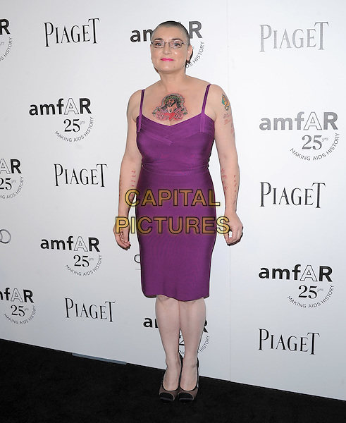 Sinead O'Connor.The amfAR's Inspiration L.A. Gala held at The Chateau Marmont in Hollywood, California, USA..October 27th, 2011.full length dress purple tattoos glasses pink lipstick religion religious jesus christ chest.CAP/RKE/DVS.©DVS/RockinExposures/Capital Pictures.