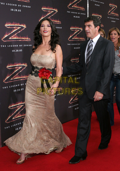 "CATHERINE ZETA-JONES & ANTONIO BANDERAS.""The Legend Of Zorro"" Premiere held at the Orpheum Theatre, Beverly Hills, California.  .October 16th, 2005.Photo Credit: Zach Lipp/AdMedia/Capital Pictures.Ref: ZL/ADM/CAP.full length beige cream lace walking red flower corsage grey gray suit pinstripe.www.capitalpictures.com.sales@capitalpictures.com.© Capital Pictures."
