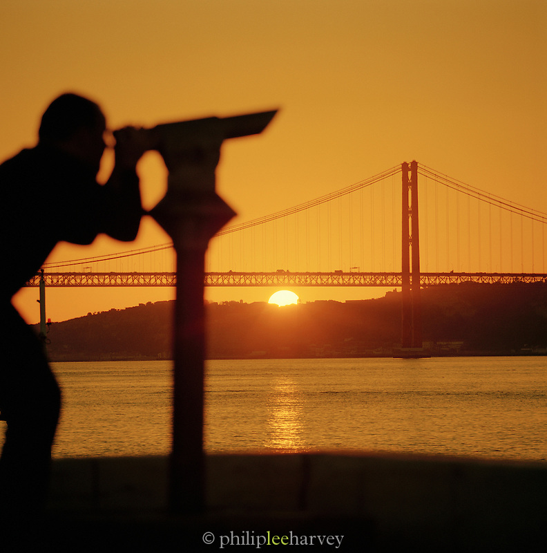 A person looks through a telescope with a vew of 25th of April bridge in Lisbon, Portugal