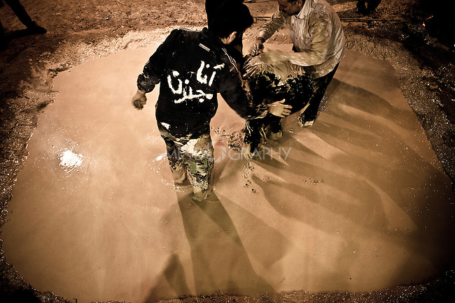 """KHORRAMABAD, IRAN : Men cover themselves in mud during the festival of Ashura. The Farsi on the jacket reads """"I'm insane for Hussein.""""..Every year to mark the death of Imam Hussein, Shia Muslims mourn for two days. In Khorramabad and Lorestan in the west of Iran, during the first day of mourning, called Tasooa, women take a vow of silence and go through the streets with the children lighting candles. At 4 am on Ashura, the second day, men cover themselves in mud and then stand in front of a fire until the mud has dried to clay. After this they go to the mosque and pray...Photo by Farhad Babaei/Metrography"""