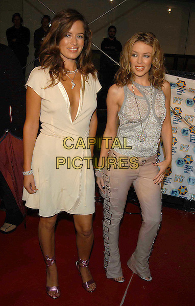 JADE JAGGER, KYLIE MINOGUE.Arrivals at the MTV Europe Music Awards.www.capitalpictures.com.sales@capitalpictures.com.©Capital Pictures.cream chiffon wrap dress, plunging neckline, fuschia pink ribbon tied shoes, back to front vest, metallic, buckles, medallion
