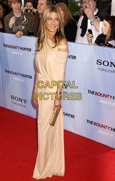 JENNIFER ANISTON .'The Bounty Hunter' New York Premiere held at the Ziegfeld Theatre, New York , NY, USA, 16th March 2010..arrivals full length wearing Donna Karen long maxi Grecian draped jersey dress  beige off the  shoulder cut out gold bracelets bracelet clutch bag .CAP/ADM/AC.©Alex Cole/AdMedia/Capital Pictures.