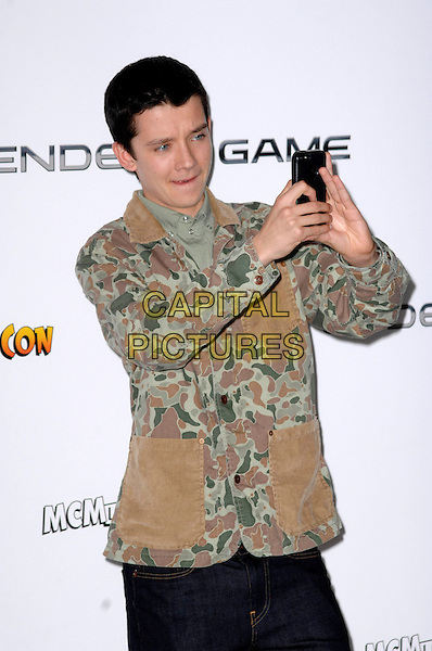 Asa Butterfield<br /> The &quot;Ender's Game&quot; fan event &amp; photocall, Odeon Leicester Square cinema, Leicester Square, London, England.<br /> October 7th, 2013<br /> half length green yellow beige brown camouflage jacket taking picture photograph <br /> CAP/PP/GM<br /> &copy;Gary Mitchell/PP/Capital Pictures