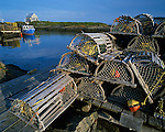 Lunenburg County, Nova Scotia, Canada: Lobster traps stacked on the dock at Blue Rocks village, with blue fishing boat and cabin in the distance