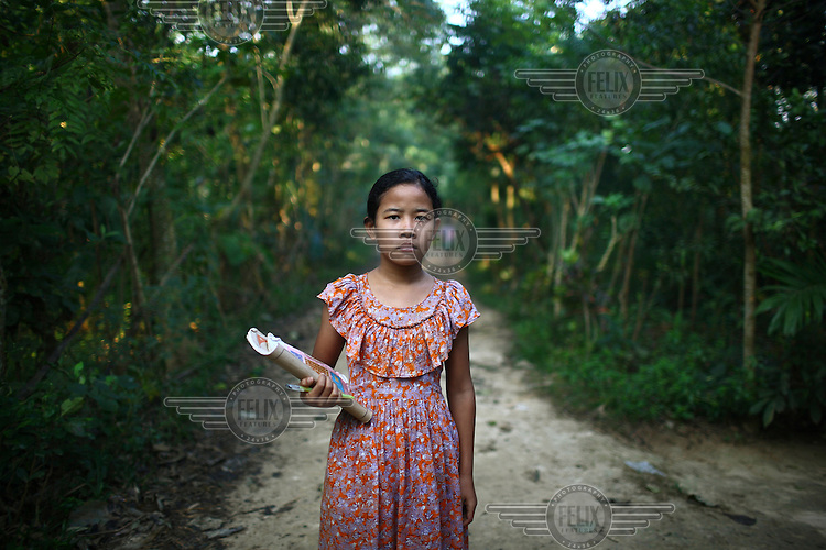 A young Garo school girl holding her text books. The Garo (or Mandi, as they refer to themselves) are an ethnic minority thought to be of Tibeto-Burmese origin. Prior to British rule they were mostly anamists but missionary work led the majority to convert to Christianity. The Garo of the Madhupur forest have long been under the threat of eviction by the government and the forest that they gain much of their livelihood from is being rapidly destroyed by unregulated logging.