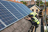 Workers install photovoltaic solar panels on the slate roof of a Victorian house in London, England.